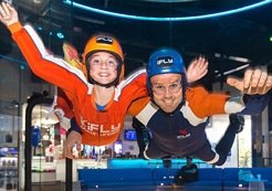Adult man and female child indoor skydiving