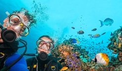 Man & Woman underwater Scuba Diving surrounded by fish and reef